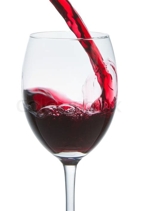Red wine pouring into wine glass isolated | Stock Photo